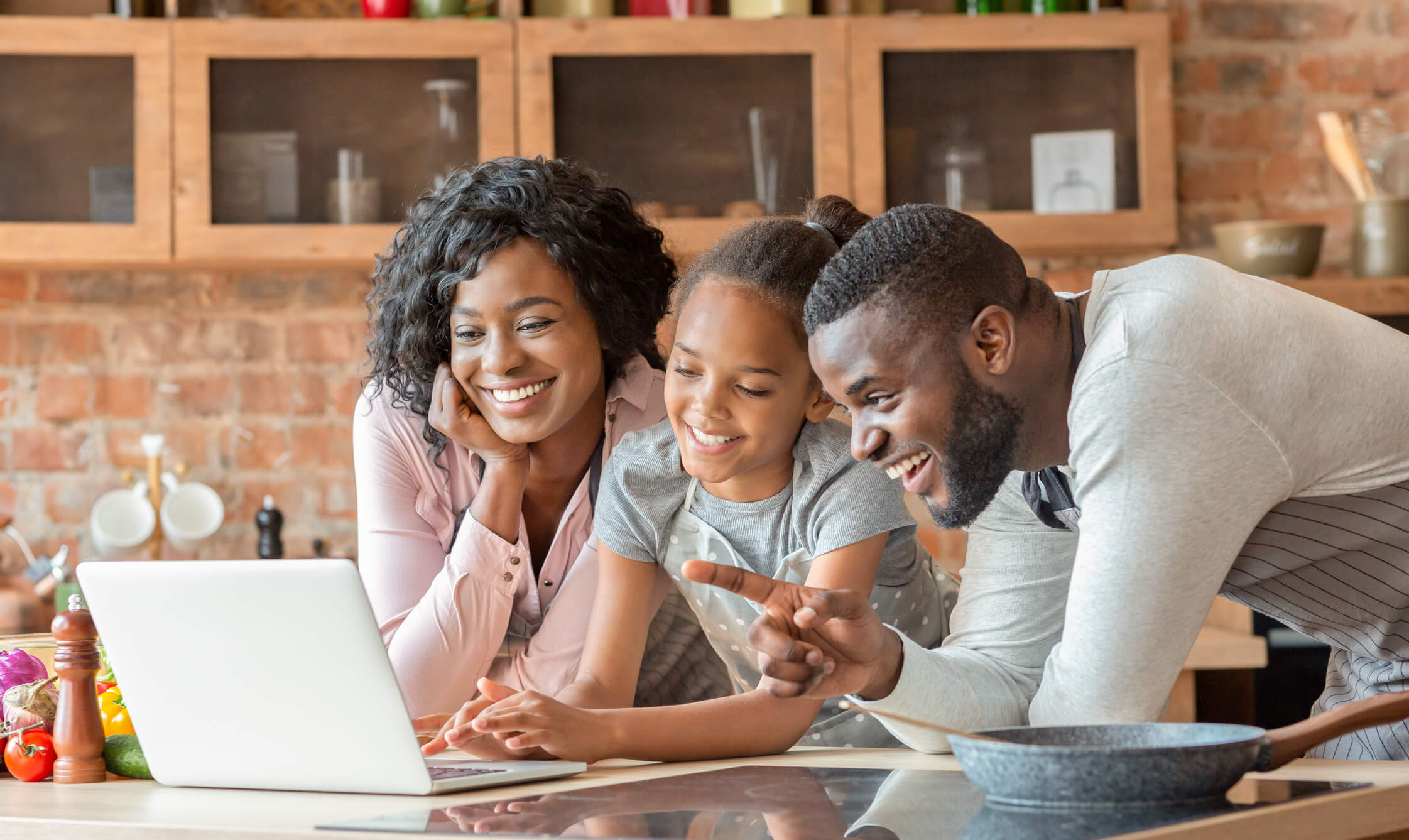 Parents and child looking at a laptop screen together