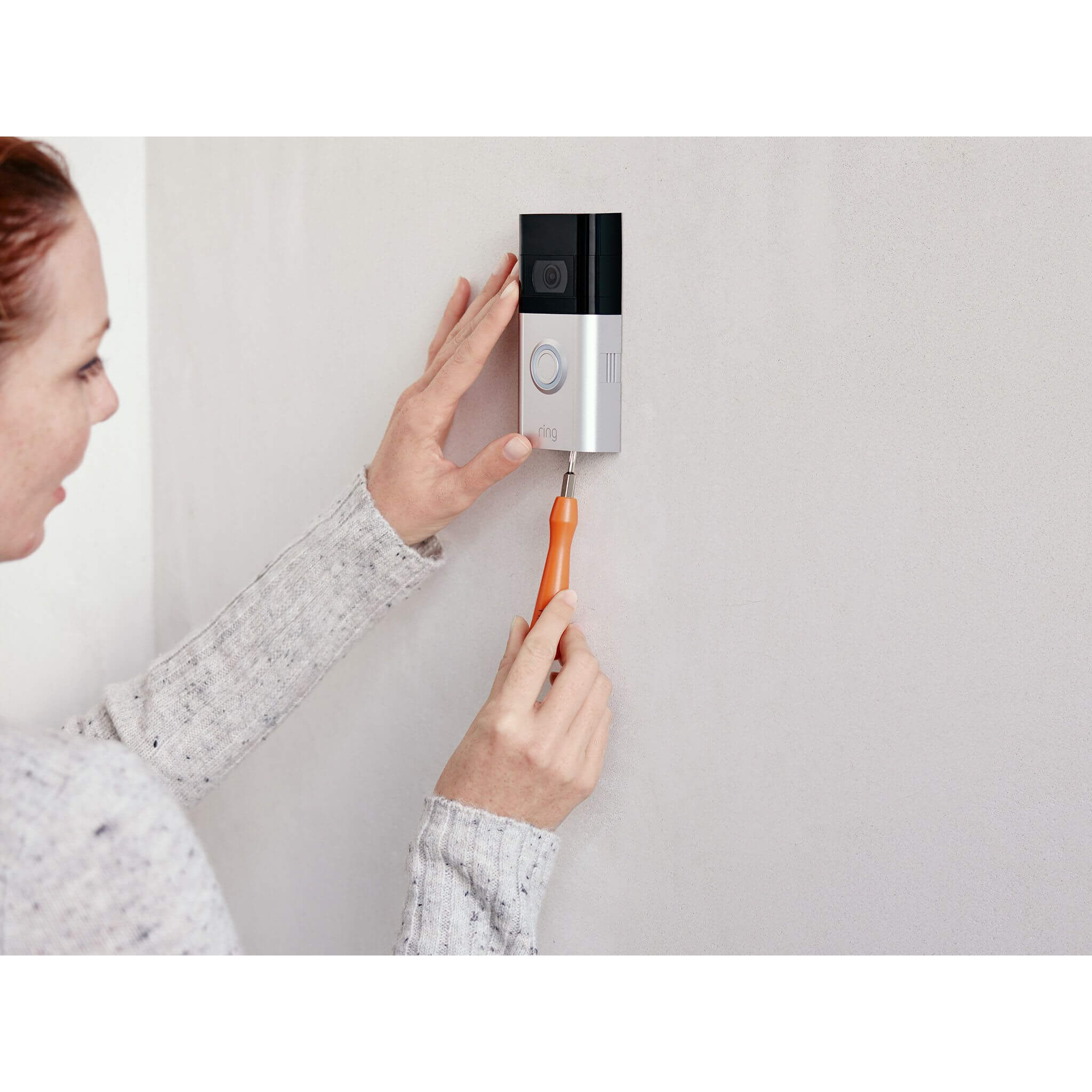 Woman installing a Ring Video Doorbell