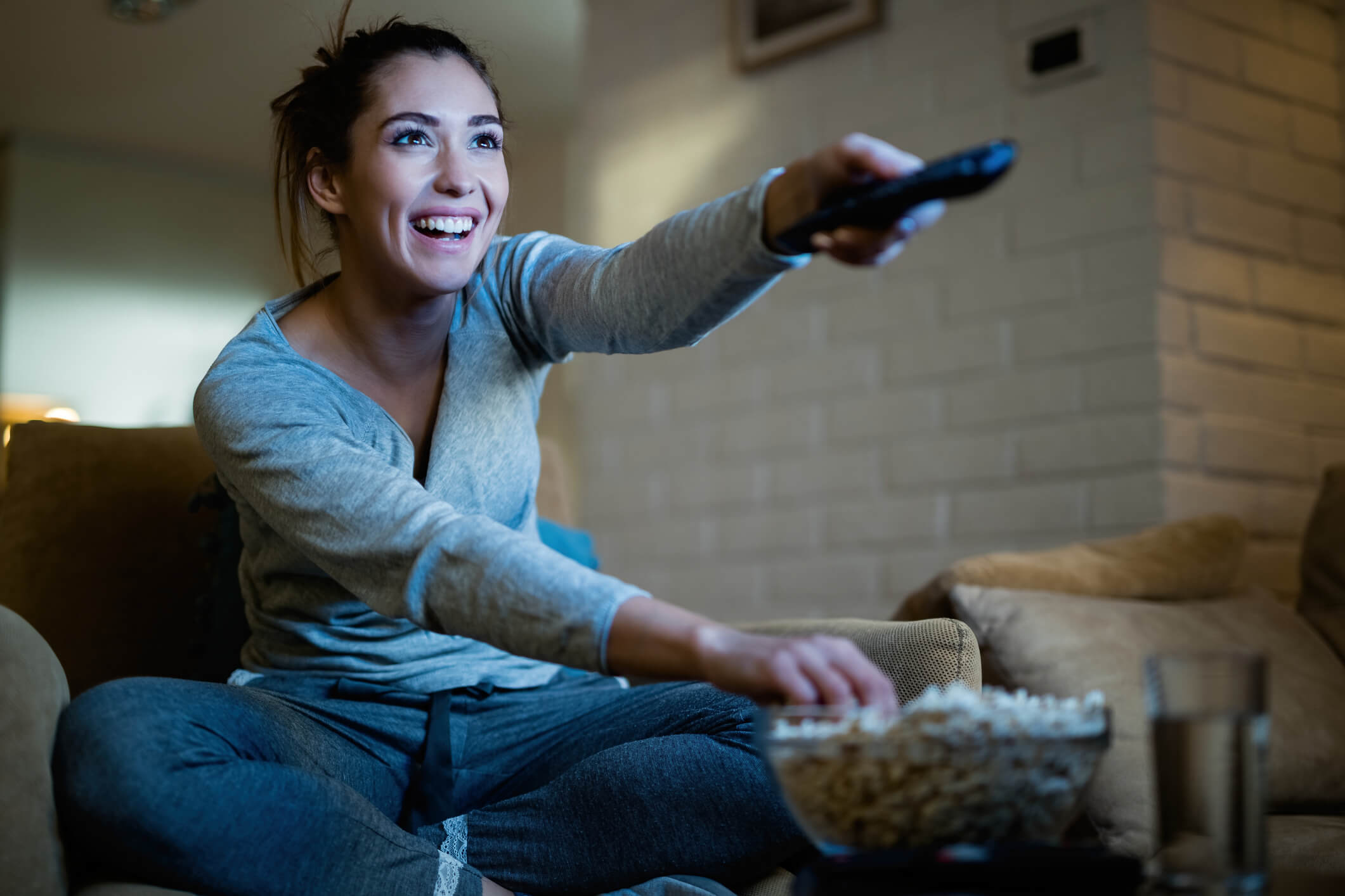 Woman on couch watching Amazon Fire TV