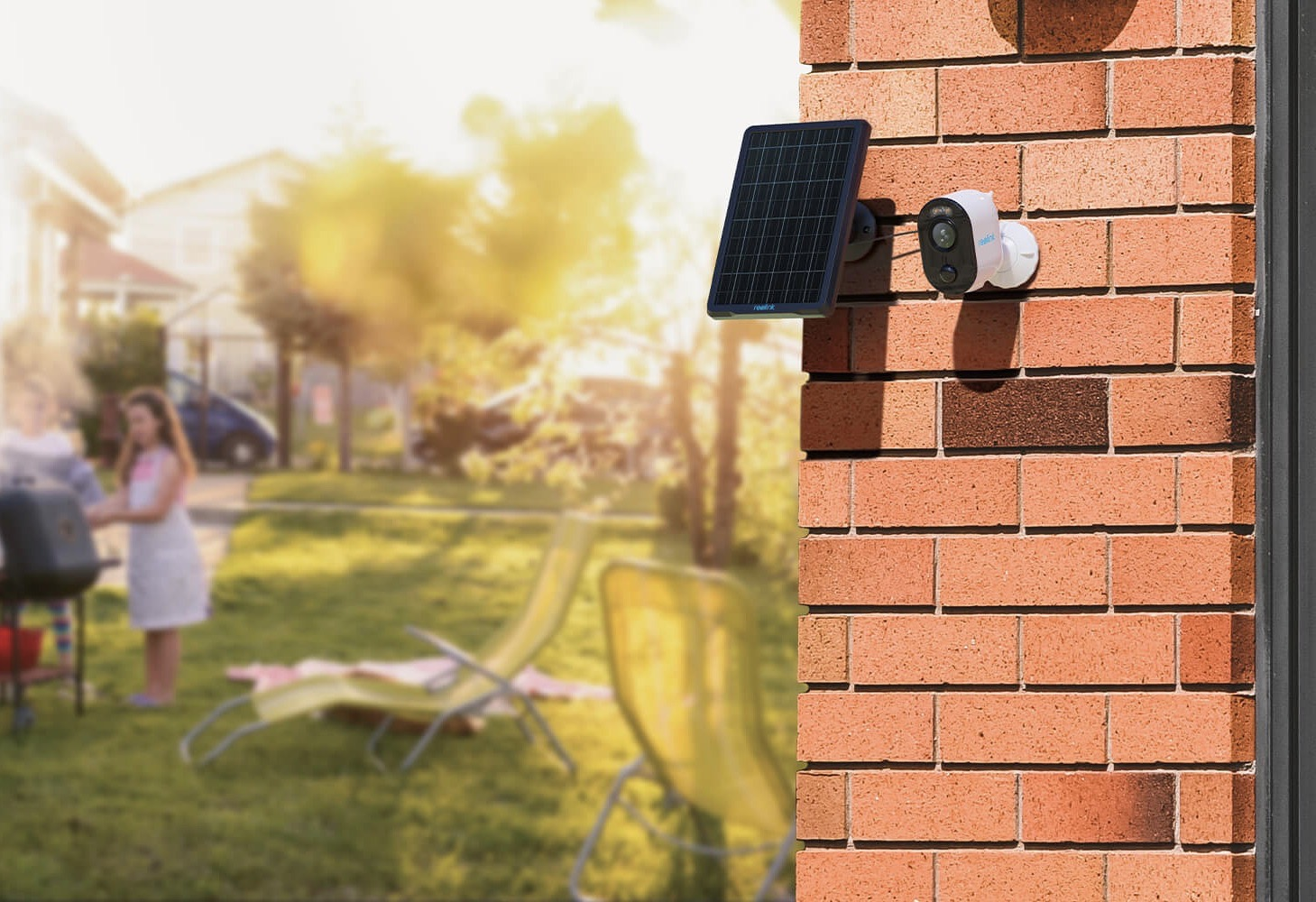 Reolink Argus 3 and solar panel mounted on a brick wall near a yard