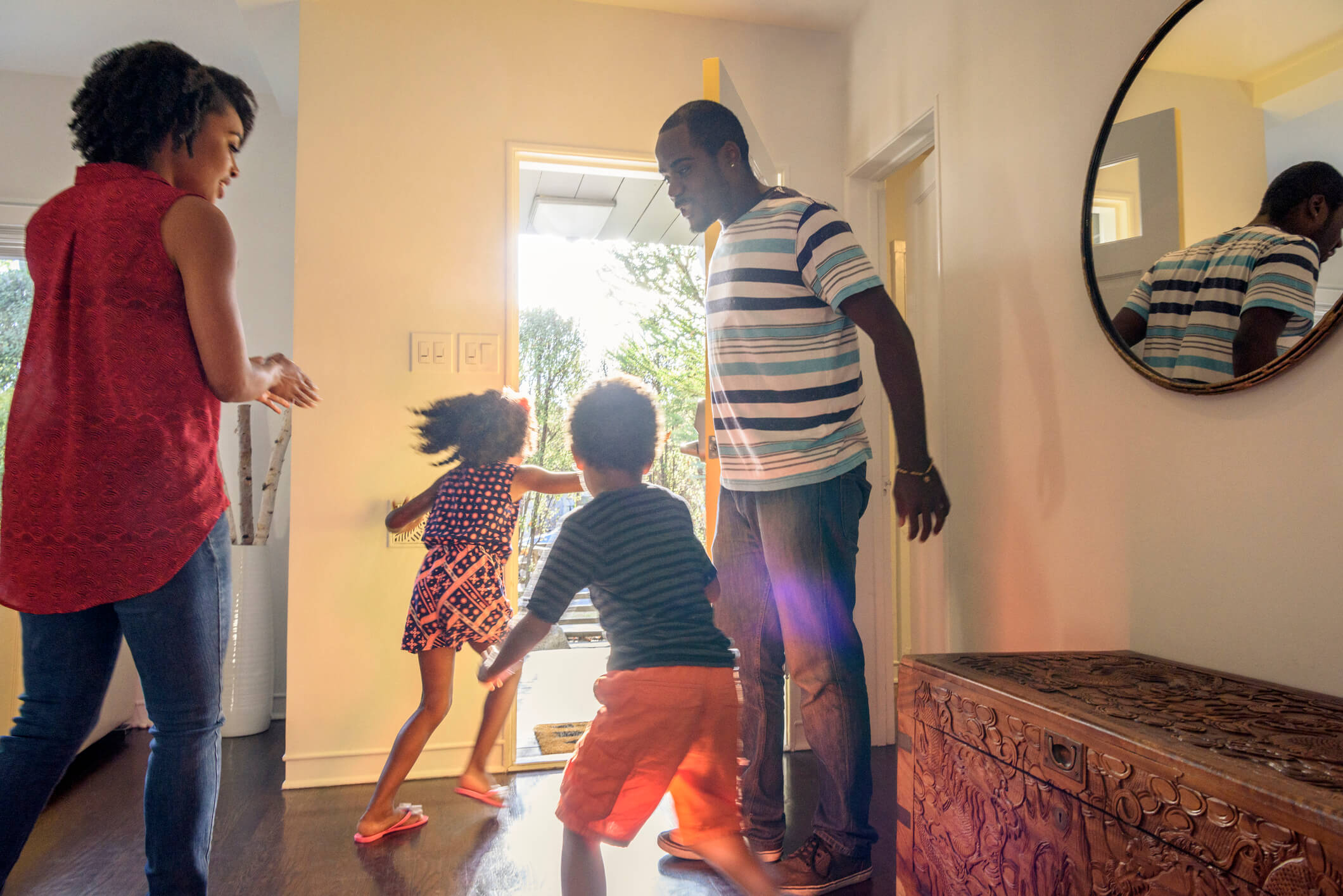 A father holds open the front door of a house as his family moves to go out the door