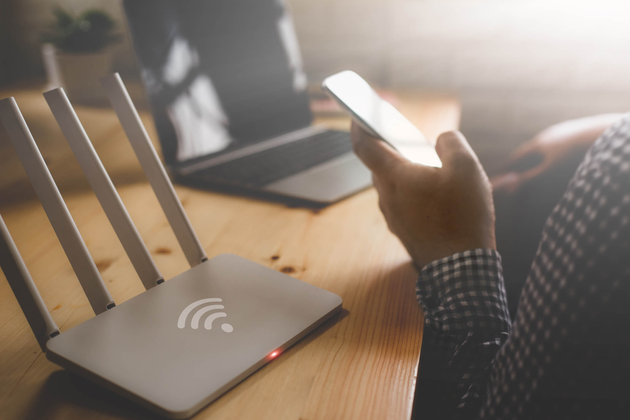 A router and a laptop sit on a desk. A hand is hold a cellphone, but the rest of the person is off frame