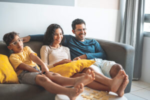 Hispanic mom, dad, and son watching TV sitting on living room couch