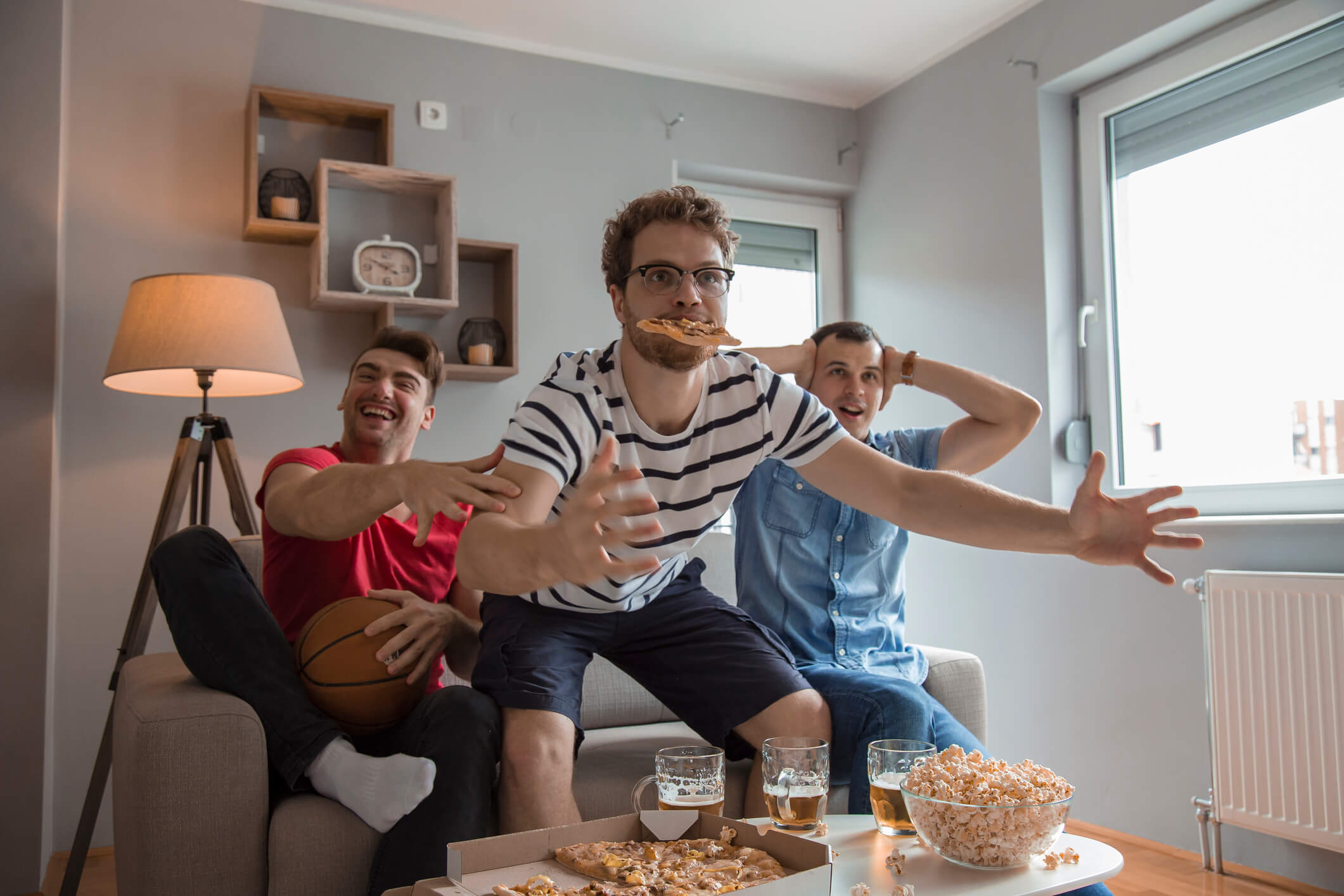 Group of friends watching basketball in living room while drinking beer and eating pizza and popcorn