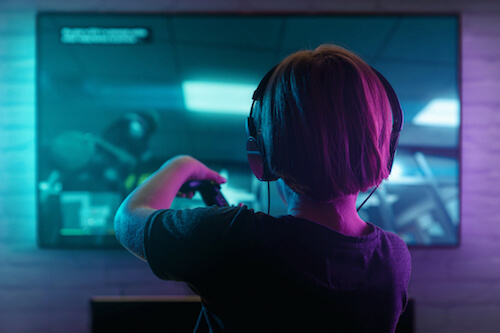 A little boy plays Xbox video games on a big-screen TV