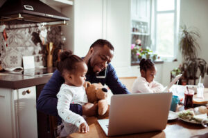 A Black father and his two daughters work and play at home