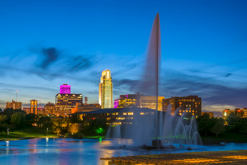 Downtown Omaha, Nebraska, at sunset with a skyline view of the Heartland of America Park