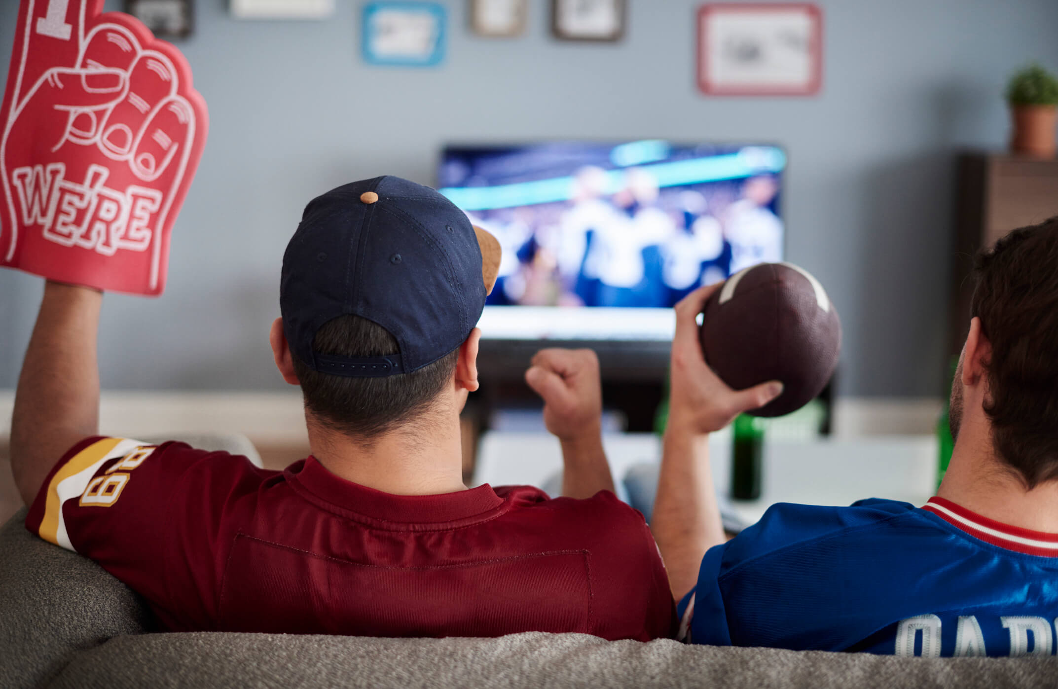 Two guys sitting on couch wearing football jerseys watching the game