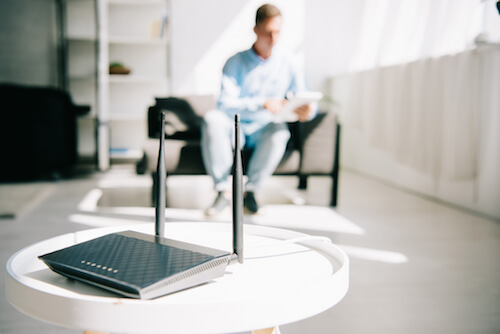 An internet router sits on a table in a living room with a man in a chair in the background