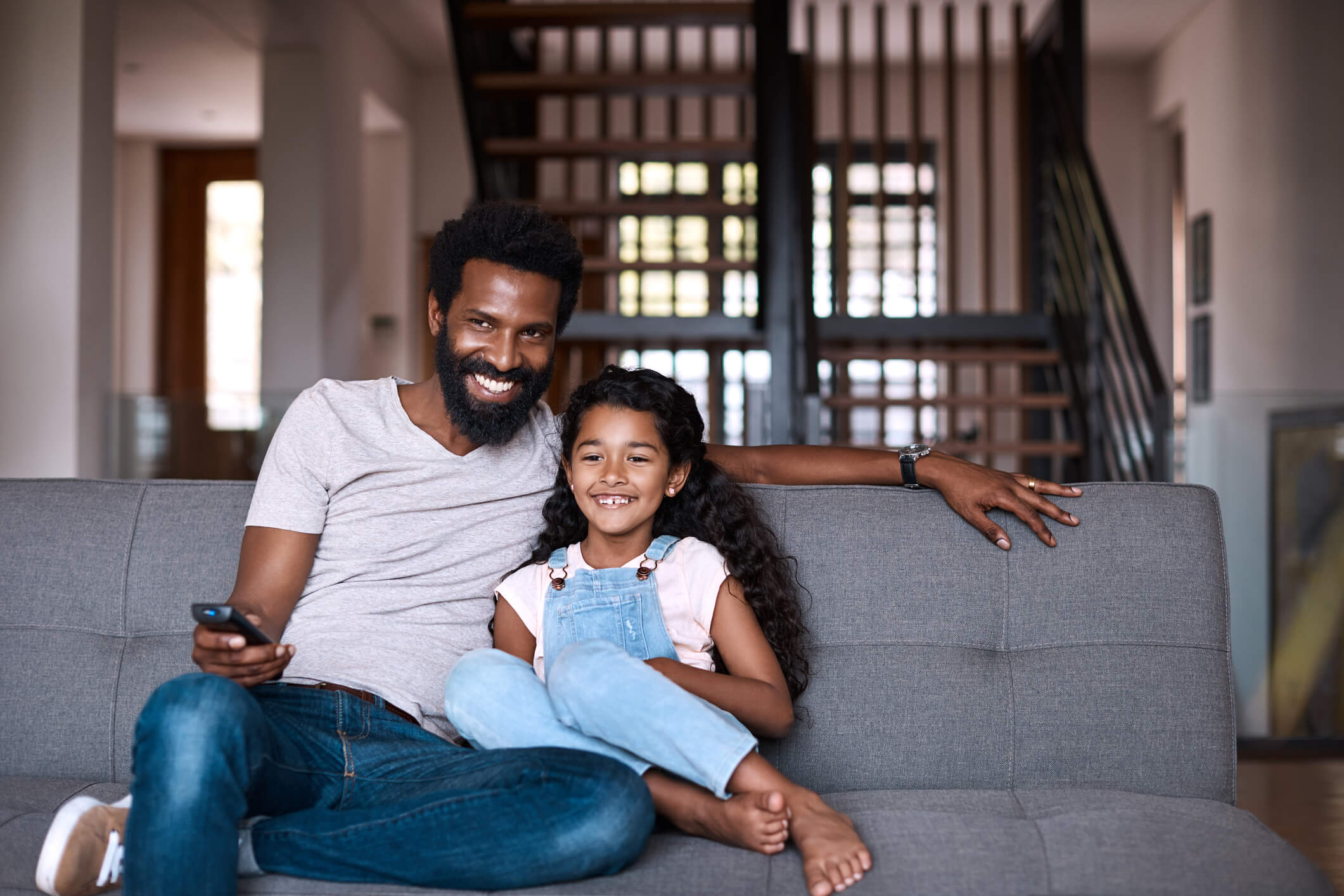 Dad and daughter sitting and smiling on living room couch watching TV