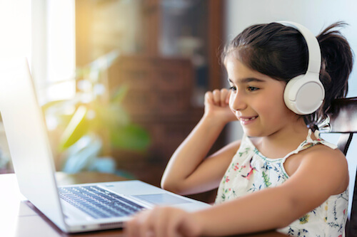 A young girl wears headphones and looks at her laptop