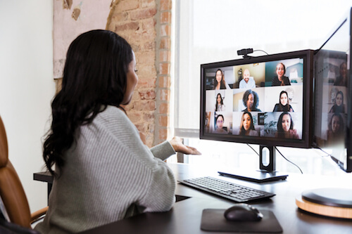 A woman sits at a desk and talks to her coworkers through video chat
