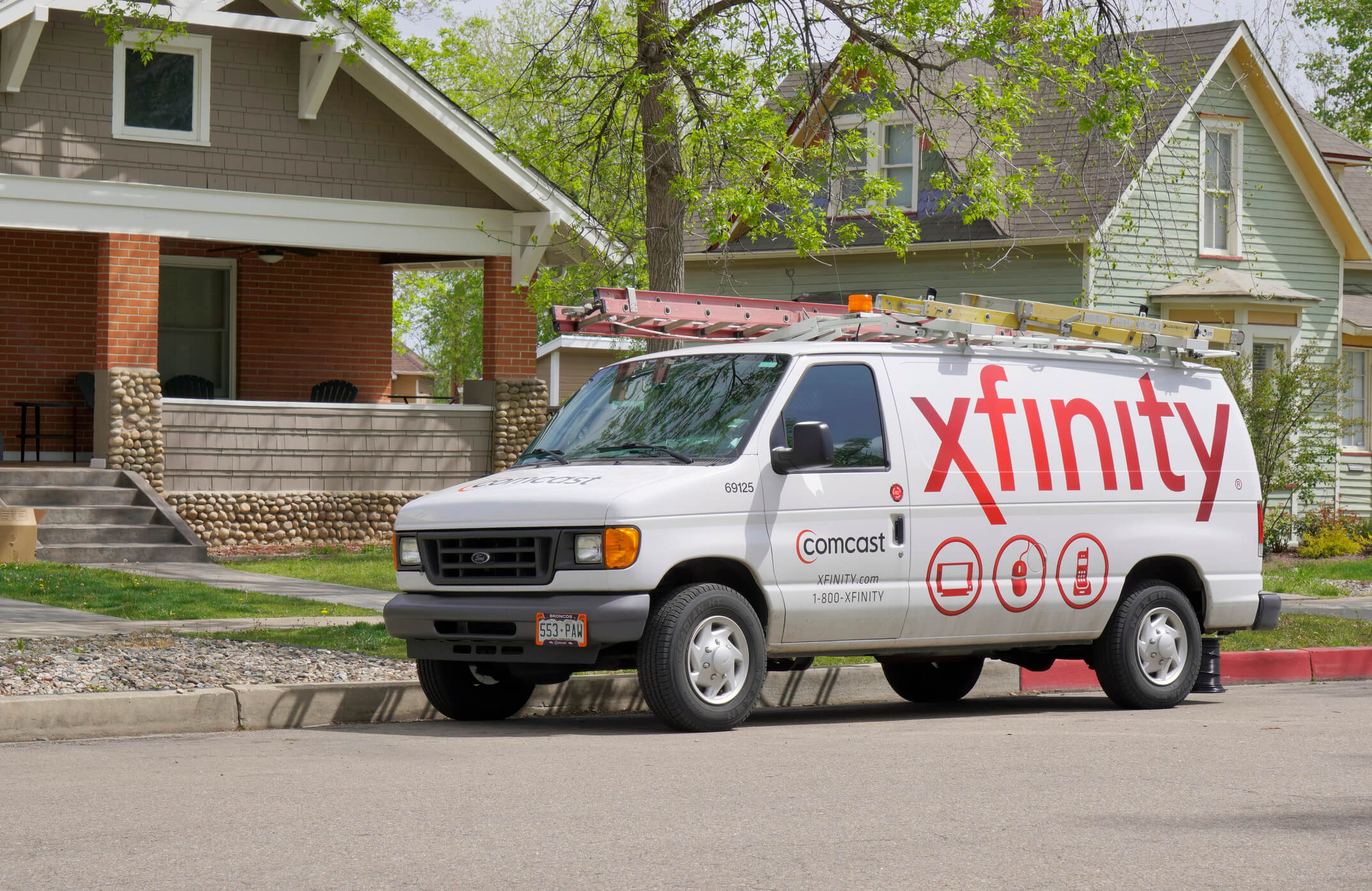 An Xfinity van parked in front of a house.