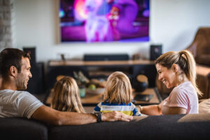 Mom, dad, daughter, and son sitting on living room couch watching TV (1)