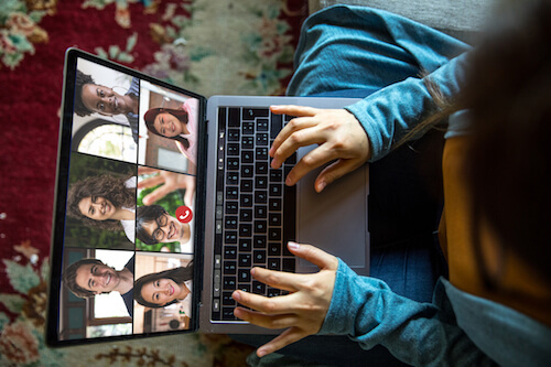 A downward view of a woman chatting in a video call on her laptop.