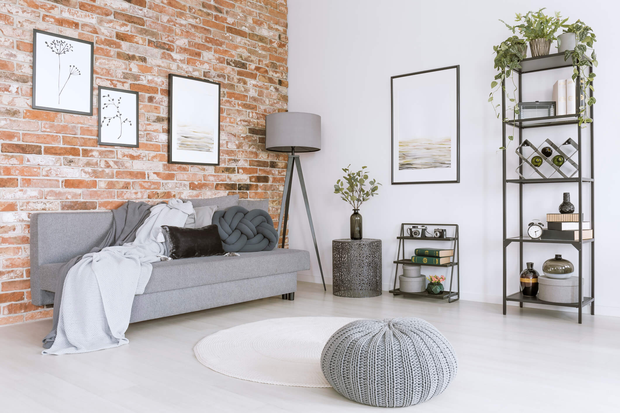 Stylish living room with a gray couch against a brick wall