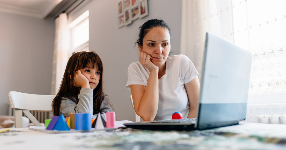 A mother and her daughter look frustrated as they stare at a laptop