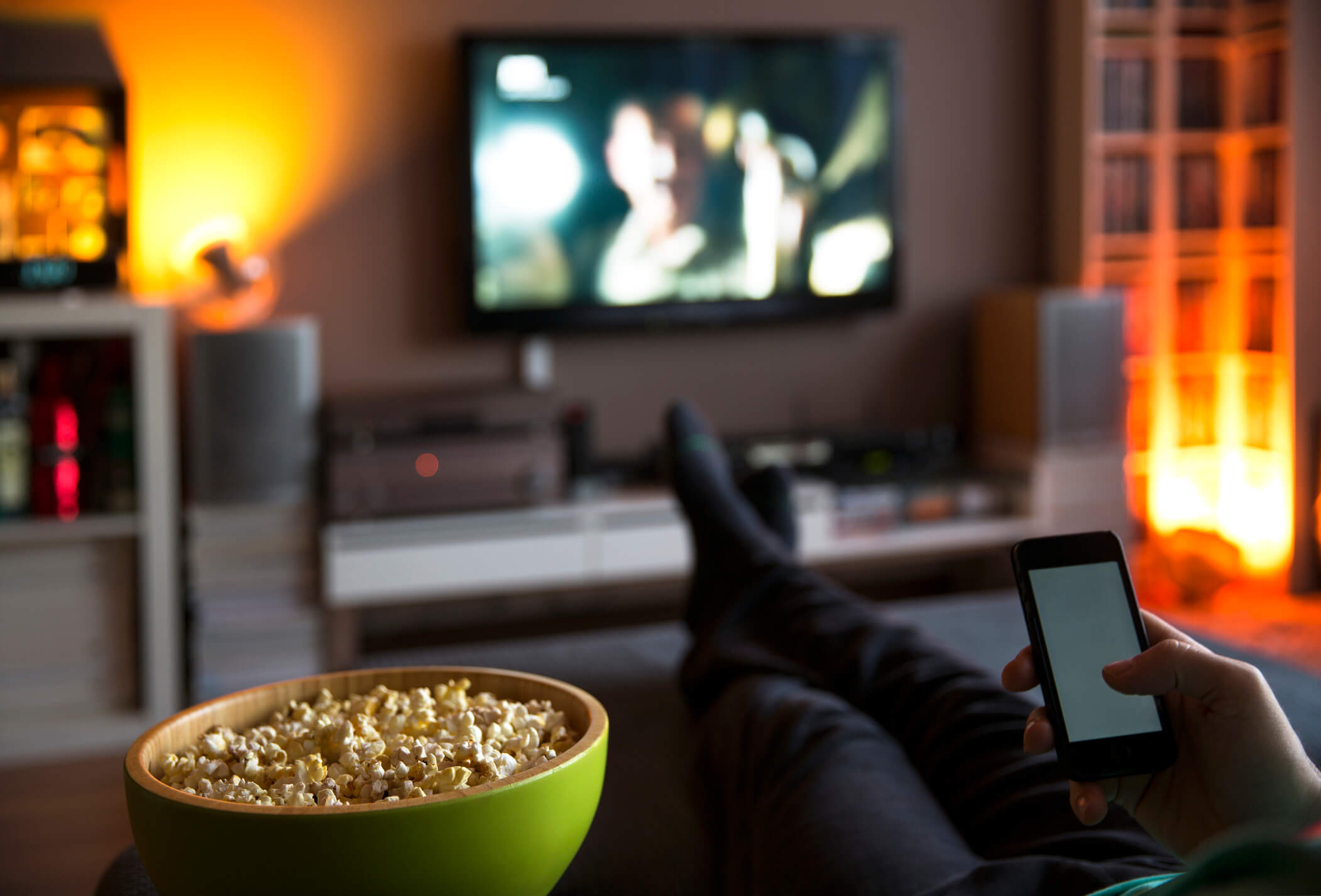 Man watching TV on living room couch eating popcorn