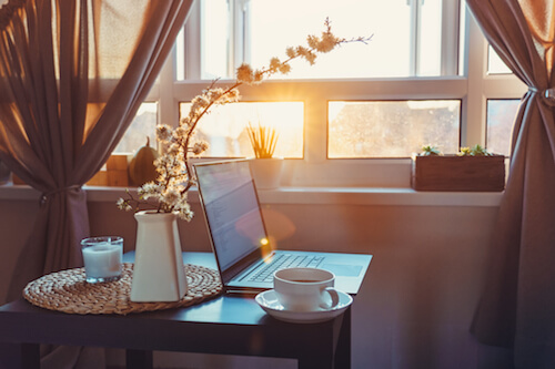 A laptop sits on a small table with a cup of coffee and a flower illuminated by sunlight