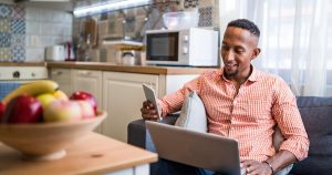 A young Black man looks at his phone and laptop while working in his kitchen