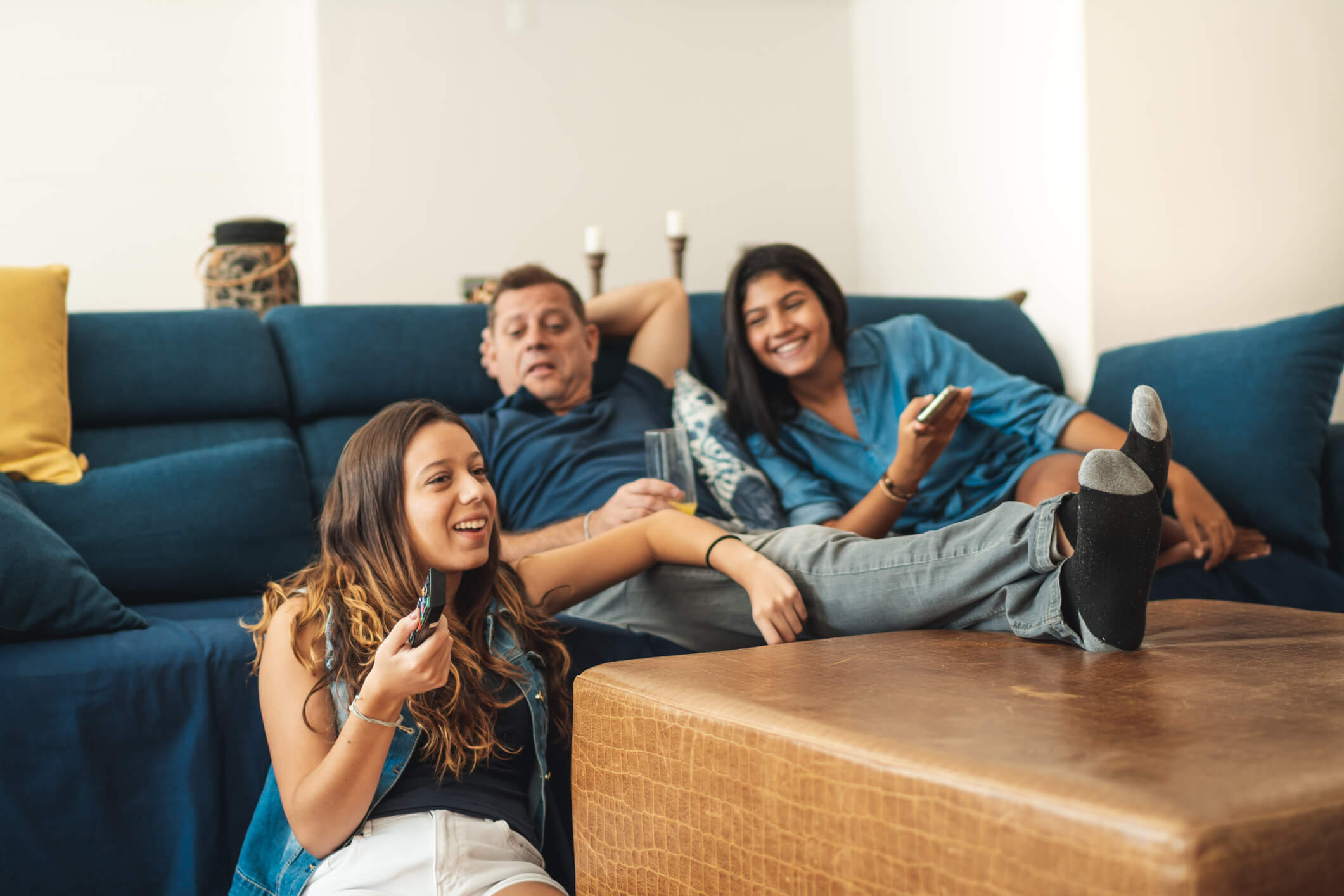 Dad and two daughters lounging on living room couch watching TV